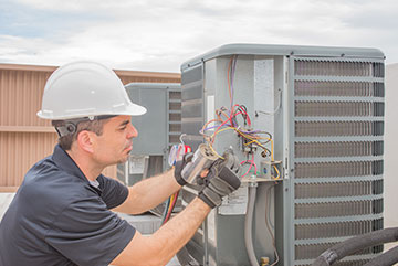 Commercial HVAC Services: AC Units, Furnaces & Chillers | Hutchens Company - commercial-hvac-maintenance-rooftop-man